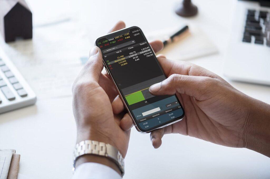 Mann handelt Aktien über sein Smartphone